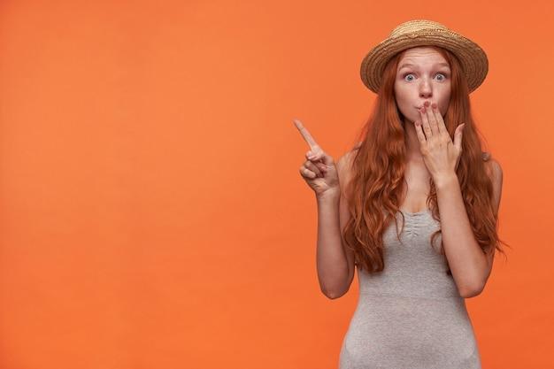 Moça atraente e atordoada com cabelo ondulado de raposa posando sobre fundo laranja em roupas casuais, levantando a mão e apontando para o lado com o dedo indicador, mantendo a palma da mão na boca e erguendo as sobrancelhas
