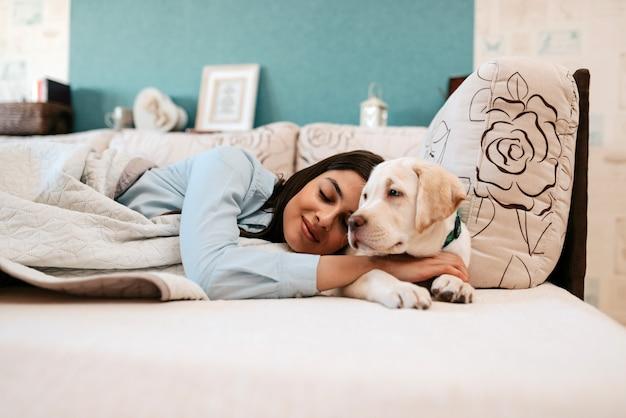 Moça atrativa com o cão que coloca em uma cama.