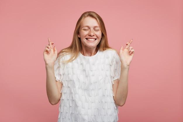 Moça bonita, alegre, com cabelo sexy, mantendo os olhos fechados enquanto faz um pedido, cruzando os dedos levantados para dar sorte e sorrindo amplamente, isolada sobre um fundo rosa