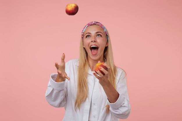 Moça bonita alegre com longos cabelos loiros fazendo malabarismos com pêssegos, se divertindo, usando bandana colorida e camisa branca