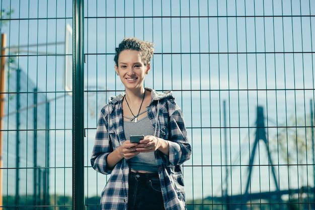 Moça bonita alegre usando roupas casuais em pé perto do campo de esportes com um dispositivo moderno