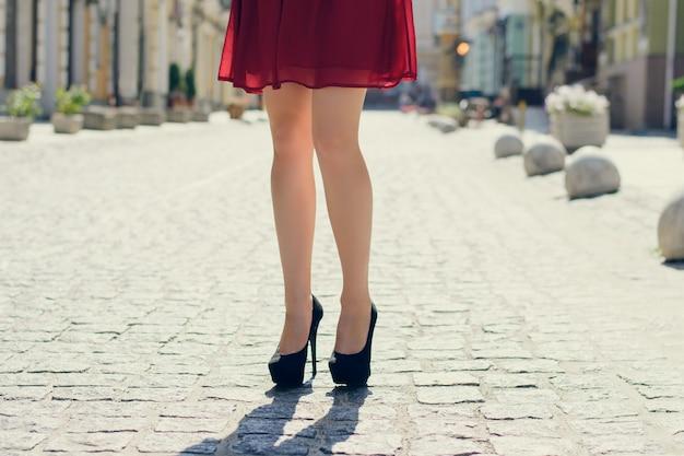 Moça bonita andando na cidade. foto de perto de pernas compridas de mulher de salto alto,