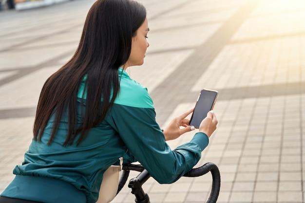 Moça bonita apoiada no guidão de uma bicicleta e usando o telefone