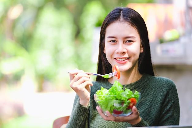 Moça bonita asiática que come o vegetal de salada