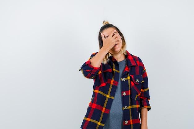 Moça bonita, cobrindo o rosto com a mão em uma camisa casual e parecendo envergonhada, vista frontal.