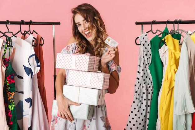 Moça bonita com a compra em pé na loja perto do cabideiro e segurando um cartão de crédito isolado em rosa