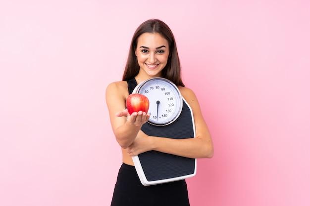 Moça bonita com a máquina de pesagem sobre a máquina de pesagem guardando cor-de-rosa isolada e oferecendo uma maçã