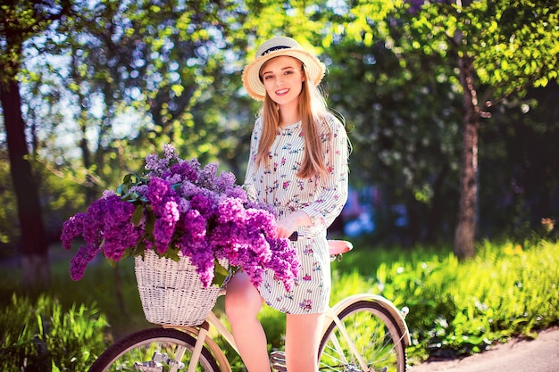 Moça bonita com bicicleta do vintage e flores na cidade na luz solar ao ar livre.