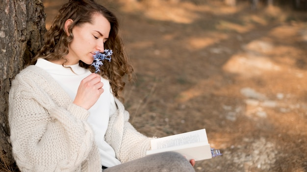 Moça bonita com cabelo encaracolado, cheirando uma flor