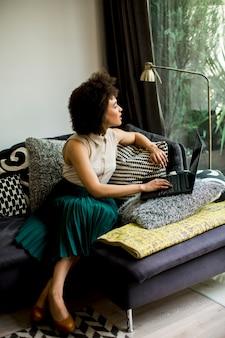 Moça bonita com cabelo encaracolado trabalhar no notebook enquanto se senta no sofá em casa