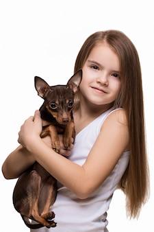 Moça bonita com o cão bonito do terrier, isolado no branco.