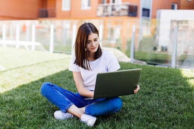 Moça bonita com o laptop ao ar livre, sentado na grama