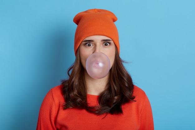 Moça bonita com olhos grandes segurando uma grande goma de mascar dentro da boca, soprando uma grande bolha