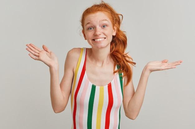 Moça bonita com rabo de cavalo ruivo e sardas, vestindo maiô colorido listrado