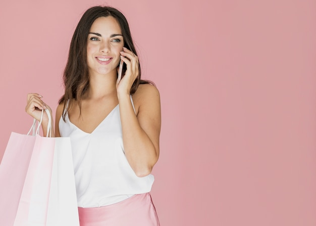 Moça bonita com redes de compras, falando no smartphone