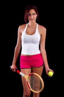 Moça bonita com uma raquete de tênis em um fundo preto.