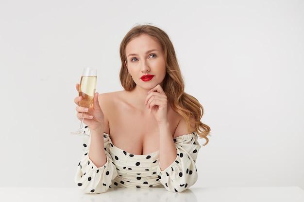 Moça bonita de longos cabelos loiros, de lábios vermelhos, segurando uma taça de champanhe, desvia o olhar pensativamente não consegue decidir qual vestido é melhor comprar. isolado sobre fundo branco.