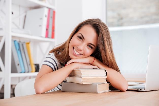 Moça bonita deita-se sobre livros na sala de aula e sorri enquanto olha para a frente