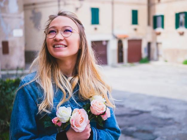 Moça bonita do tártaro nos vidros com um ramalhete das flores. feche acima do retrato de uma mulher bonita atrativa no revestimento das calças de brim que guarda o ramalhete das rosas. foco seletivo