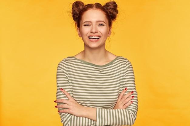 Moça, bonita e engraçada mulher ruiva com dois pães. vestindo um suéter listrado e rindo com as mãos cruzadas sobre o peito. fique isolado sobre a parede amarela
