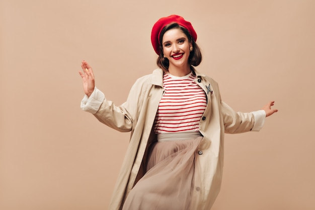 Moça bonita em roupa bege, dançando no fundo isolado. mulher bonita e elegante com lábios vermelhos na boina brilhante, saia longa e sorrisos de capa.