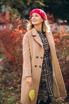 Moça bonita em um barrete vermelho fora no parque