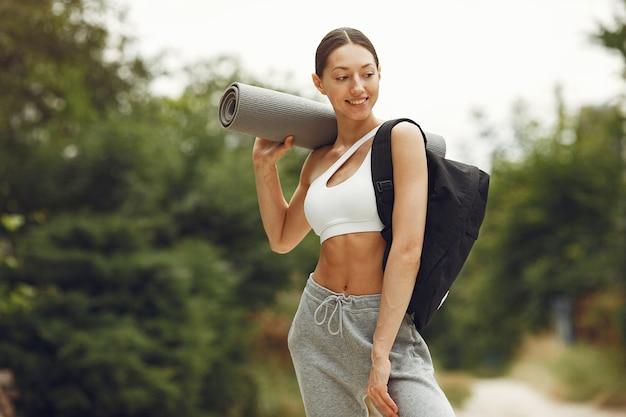 Moça bonita em um parque. morena se prepare para a ioga. garota em um traje esportivo.