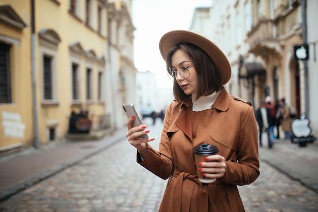 Moça bonita, falando no celular, caminhando ao ar livre em dia frio de outono