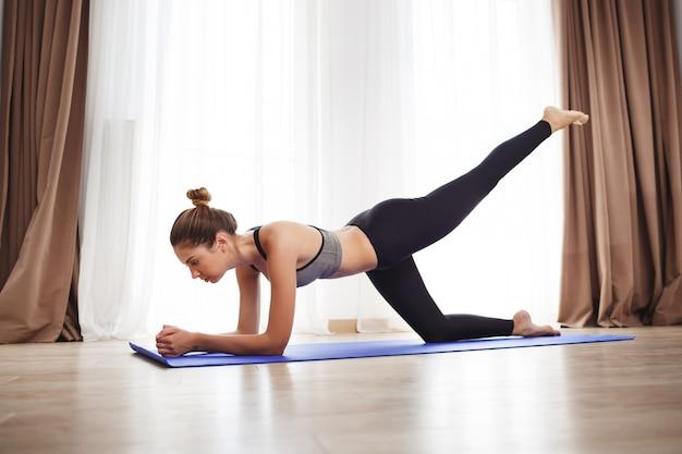 Moça bonita faz exercícios de ioga no chão