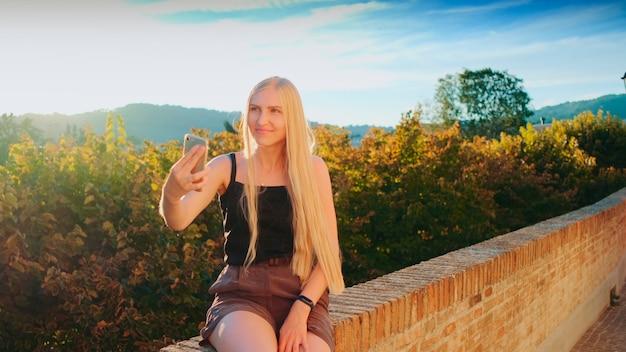 Moça bonita, fazendo selfie em smartphone em frente a uma bela paisagem natural. viagem de verão para outro país.