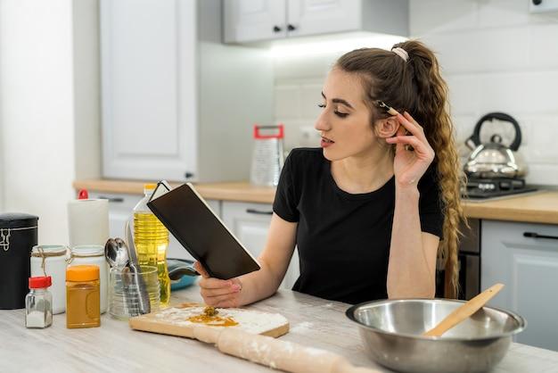 Moça bonita lendo caderno com receita