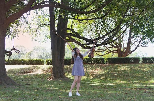 Moça bonita levanta violino e curva-se, com sentimento feliz, retrato de modelo posando, em um parque, reflexo da luz do sol brilhando ao redor