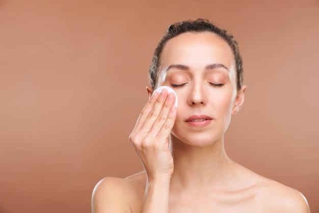 Moça bonita limpando o rosto com loção tonificante pela manhã ou após a remoção da maquiagem à noite