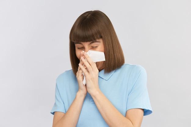 Moça bonita mal espirrando o nariz no lenço de papel com camisa azul na parede cinza