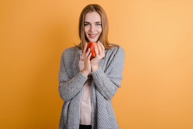 Moça bonita na camisola quente comendo maçã verde, olhando na câmera sobre fundo laranja colorido