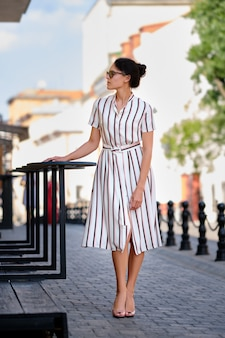 Moça bonita no vestido listrado na cidade em dia de sol