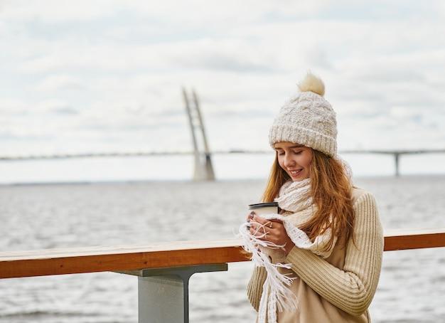 Moça bonita que bebe o café, chá de uma caneca plástica no outono, inverno.