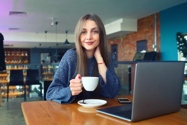 Moça bonita que descansa em um café