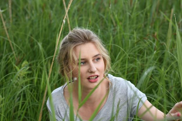 Moça bonita que descansa em uma noite de verão na natureza e na cidade