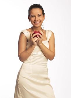 Moça bonita que entrega lhe uma maçã vermelha de vista saudável. isolado no branco.