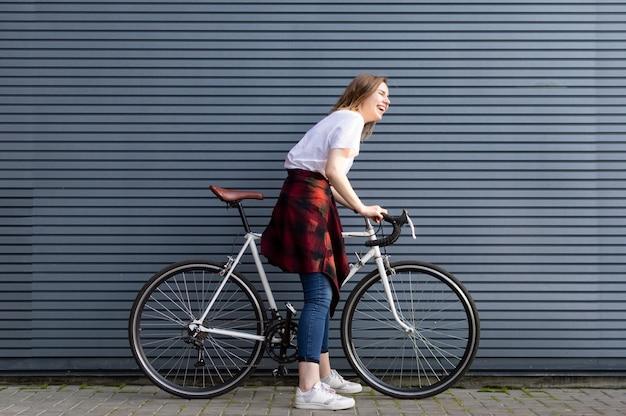 Moça bonita que está com uma bicicleta branca no fundo da parede listrada cinza