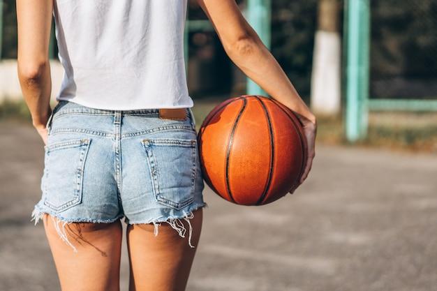 Moça bonita que guarda a bola do basquetebol, vista traseira.