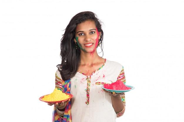 Moça bonita que guarda a cor pulverizada na placa por ocasião do festival de holi.