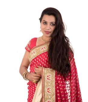Moça bonita que levanta no saree tradicional indiano no fundo branco.