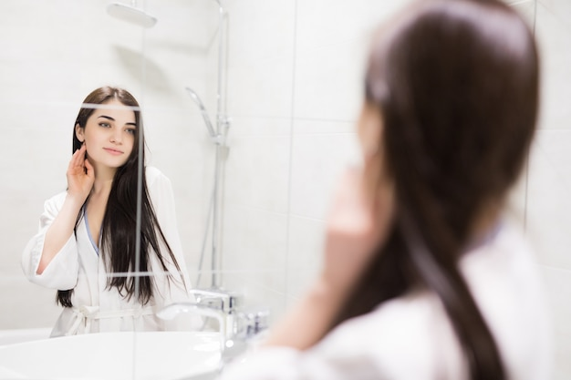 Moça bonita que olha no reflexo no espelho que fica no banheiro