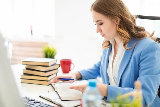 Moça bonita que senta-se na mesa no escritório, guardando uma pena em sua mão e lendo um livro.