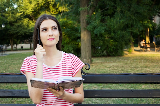Moça bonita que senta-se no banco de madeira no parque e que pensa com um livro