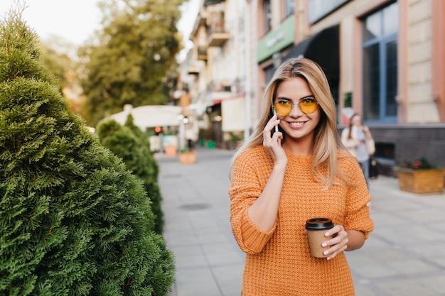 Moça bonita rindo falando ao telefone enquanto caminhava por arbustos com uma xícara de chá