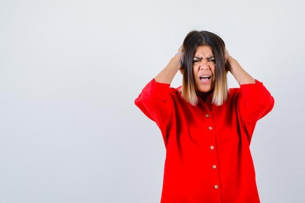 Moça bonita segurando as mãos nas orelhas na blusa vermelha e parecendo irritada, vista frontal.