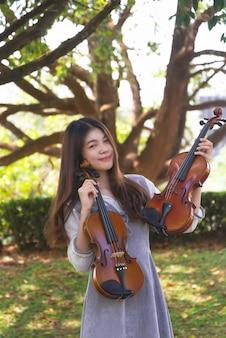 Moça bonita segurando dois violinos na mão, mostra detalhes do instrumento acústico